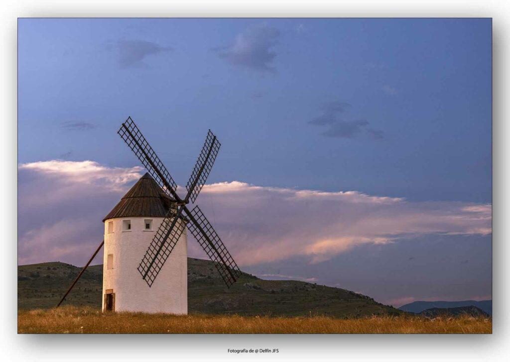 hermosa fotografía del molino de viento de malanquilla al atardecer en un día con nuves muy bonitas